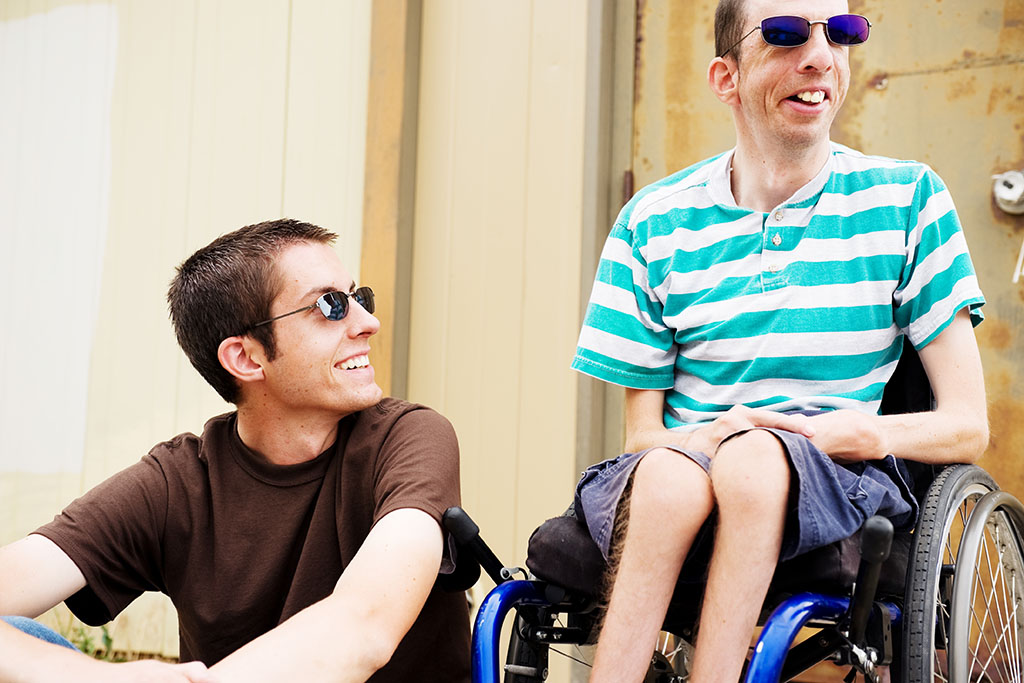 Two young men wearing sunglasses and summer clothing sit next to one another. The man on the right is in a wheelchair. Both are smiling.